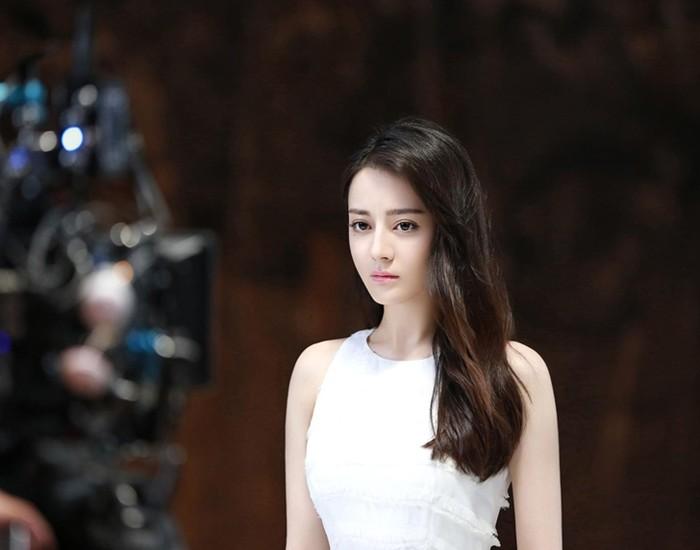 近日,迪丽热巴一组拍摄花絮照曝光,白衣长发清纯可爱,女神范儿十足