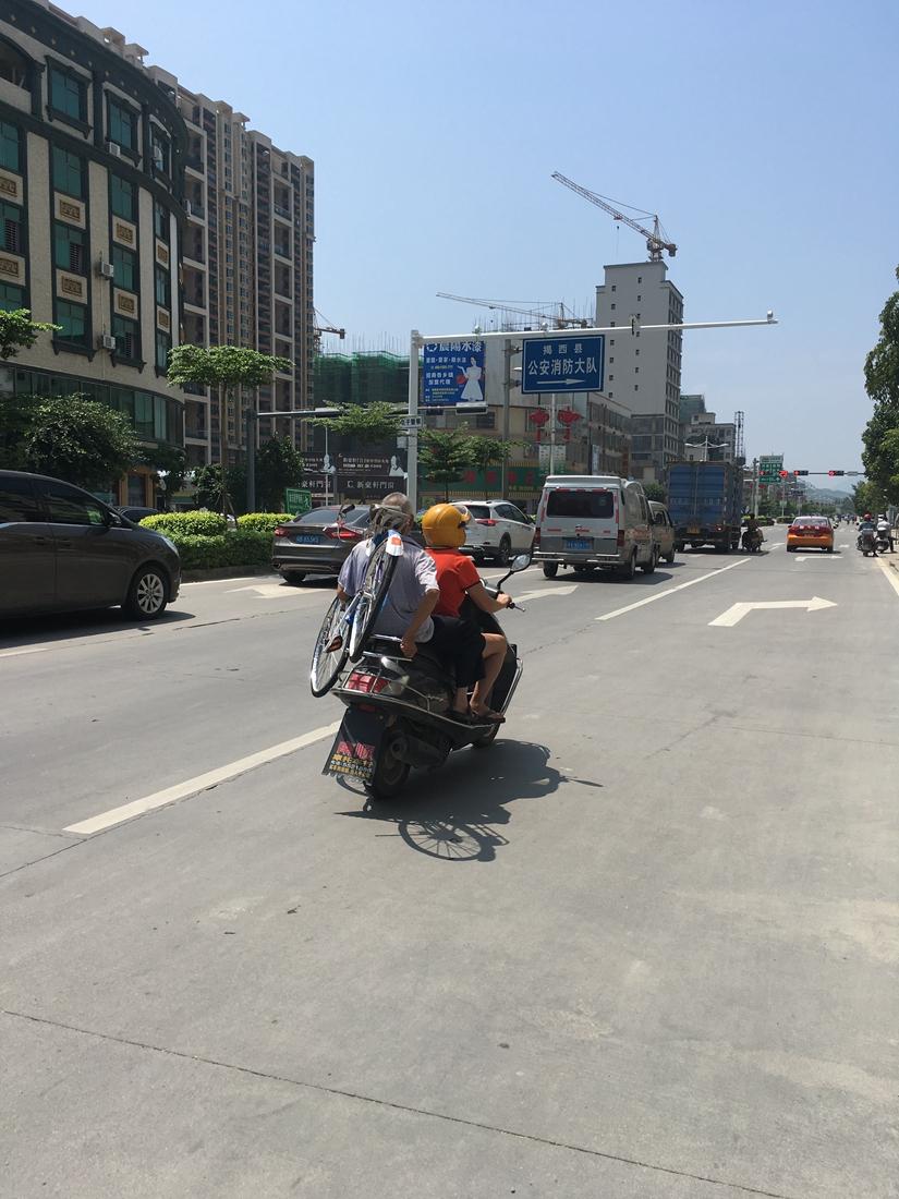 路上一个老叔扛着一辆单车