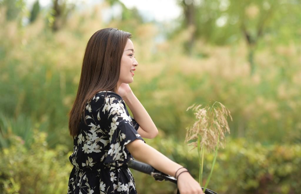 草坪上迷人的穿黑色花裙的姑娘,外景拍摄